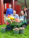 Mann und zwei Frauen mit geerntetem Gemüse Stockfotos