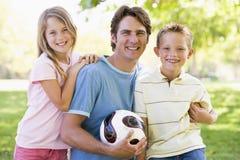 Mann und zwei junge Kinder, die Volleyball anhalten Stockfoto