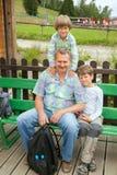 Mann und zwei Jungen sitzen auf Bank lizenzfreie stockfotografie