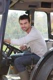 Mann ungefähr, zum des Traktors anzutreiben Stockfotos