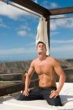 Mann unter dem Himmel, der Meditation tuend sich entspannt Stockfoto