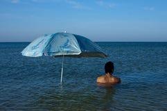Mann unter einem Regenschirm Stockbild