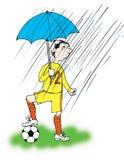 Mann unter Regenschirm plaing den Fußball Stockbild