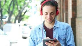 Mann unter Verwendung der digitalen Tablette und der hörenden Musik stock video