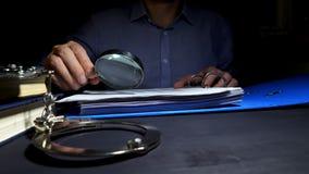 Mann unter Verwendung der Lupe für Kontrollgeschäftsunterlagen für Untersuchung Steuerhinterziehung stock footage