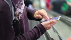 Mann unter Verwendung des intelligenten Telefons auf Rolltreppe stock video footage