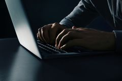 Mann unter Verwendung des Laptops bei Tisch auf dunklem Hintergrund KRIMINELLE AKTIVIT?T stockbilder