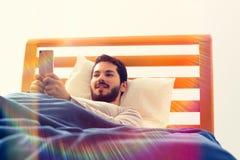 Mann unter Verwendung des Smartphone im Bett Morgen Lizenzfreie Stockfotografie
