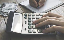 Mann unter Verwendung des Taschenrechners, der zählt, Anmerkungen an der Bürohand machend, ist schreibt in ein Notizbuch lizenzfreies stockbild