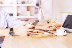 Mann unter Verwendung des Telefons und des Laptops Lizenzfreies Stockfoto