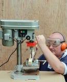 Mann unter Verwendung einer Bohrgerätpresse auf Holz Lizenzfreies Stockbild