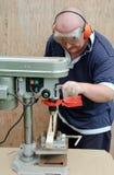 Mann unter Verwendung einer Bohrgerätpresse auf Holz Stockfoto