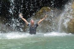 Mann unter Wasserfallfluß stockfotos