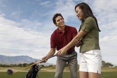 Mann-unterrichtende Frau, zum des Golfs zu spielen Stockbilder