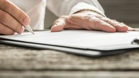 Mann in unterzeichnendem Geschäftsdokument des weißen Hemdes Lizenzfreie Stockfotografie