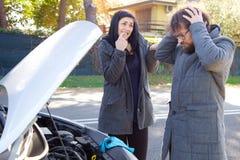 Mann verärgert mit der Frau, die Automotor gebrochen ist Lizenzfreie Stockfotos
