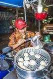 Mann verkauft köstliche Mehlklöße am Markt im Freien Stockbild