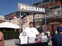 Mann verkauft Programme außerhalb des Baseballstadions vor Spiel Lizenzfreies Stockfoto
