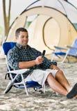 Mann-Versenden von SMS-Nachrichten auf Handy am Campingplatz Stockbild