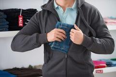 Mann-versteckende Jeans in der Jacke am Speicher Lizenzfreies Stockfoto