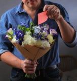 Mann versteckt eine Anmerkung im Blumenstrauß Stockfotografie