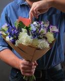 Mann versteckt eine Anmerkung im Blumenstrauß Lizenzfreie Stockfotografie