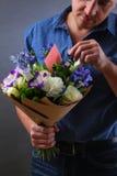 Mann versteckt eine Anmerkung im Blumenstrauß Lizenzfreies Stockfoto