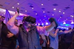 Mann versucht Kopfhörer- und Handkontrollen der virtuellen Realität Stockbilder