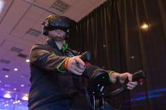 Mann versucht Kopfhörer- und Handkontrollen der virtuellen Realität Stockfoto