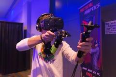 Mann versucht Kopfhörer- und Handkontrollen der virtuellen Realität HTC Vive Stockbild