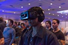 Mann versucht virtuellen Oculus-Riss-Wirklichkeitskopfhörer Stockbild