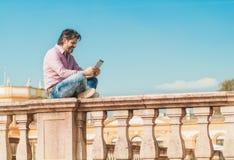 Mann in voller Länge mit digitalem Tablettensitzen und -c$simsen Stockbild