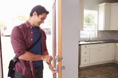 Mann-Von der Arbeit nach Hause kommen und Öffnungs-Tür der Wohnung stockfotografie