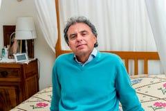 Mann von mittlerem Alter, der auf Bett sich entspannt Lizenzfreie Stockbilder