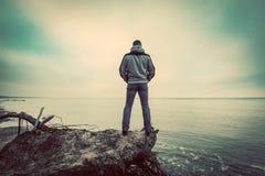 Mann von mittlerem Alter, der auf defektem Baum auf dem wilden Strand betrachtet Seehorizont steht Lizenzfreie Stockfotos