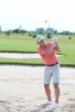 Mann von mittlerem Alter, der am Golfplatz schwingt Lizenzfreies Stockfoto