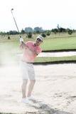 Mann von mittlerem Alter, der am Golfplatz spielt Lizenzfreie Stockfotografie