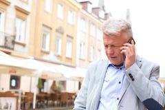 Mann von mittlerem Alter, der Handy in der Stadt verwendet Lizenzfreies Stockfoto