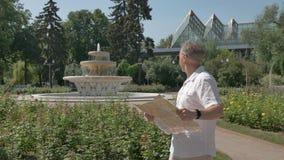 Mann von mittlerem Alter in einem weißen Hemd und große Glasblicke auf eine Papierkarte stock footage