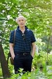 Mann von mittlerem Alter geht in einen Sommerpark stockbild