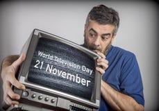 Mann von mittlerem Alter hält ein Fernsehen mit Weltfernsehtagesam 21. november Schirm stockbild