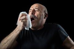 Mann von mittlerem Alter mit Grippe niesend in ein Taschentuch Stockbild