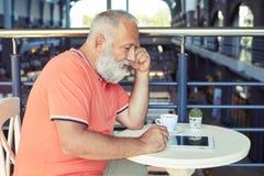 Mann von mittlerem Alter mit Tasse Kaffee- und Tabletten-PC Stockbilder