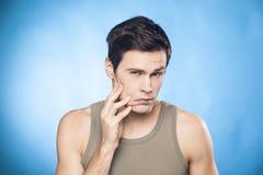 Mann vor dem Spiegel, der seine Kinnprüfung betrachtet, ist er rasierte Stockbilder
