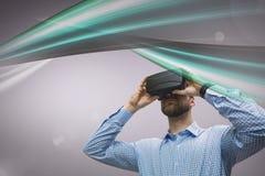 Mann in VR-Kopfhörer, der grüne Lichter gegen rosa Hintergrund betrachtet Stockfoto