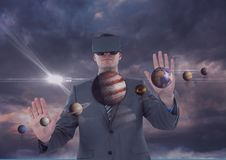 Mann in VR-Kopfhörer, der Planeten 3D gegen purpurroten Himmel mit Wolken und Aufflackern berührt Stockbild