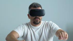 Mann in vr Kopfhörer, der Spiele, kindische Unterhaltung, Simulatoranwendung spielt stock footage