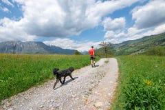 Mann während des Wegs in den Bergen mit seinem Hund, der ihm folgt lizenzfreie stockfotos