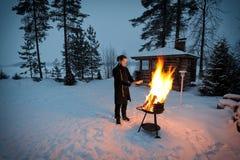 Mann wärmt sich durch das Feuer Stockfotografie