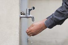 Mann wäscht seine Hände Stockfoto